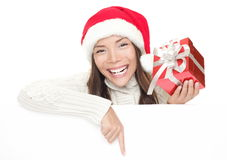 Christmas girl leaning over billboard sign. Christmas woman leaning over billboard sign. Pointing down holding gift showing big toothy smile. Caucasian / Asian royalty free stock photo