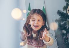 Merry Christmas! Happy little girl throws sparkles near the Christmas tree. Glitter sparkles in the air for a celebration, Happy royalty free stock photo