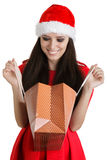 Christmas Girl Looking in Shopping Bag. Young woman in Christmas costume on white background Royalty Free Stock Photos