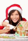 Christmas girl making Gingerbread house Royalty Free Stock Photo