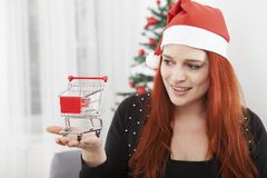 Christmas girl with mini shopping trolly cart Royalty Free Stock Photos