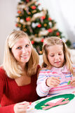 Christmas: Girl And Mother Working On Holiday Crafts. Mother and child in various Christmas themed activities in the home Royalty Free Stock Photos