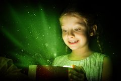Christmas. Girl opens a box of magic, sorcery, and there shines the light, Christmas miracle Stock Photography