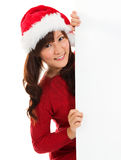 Christmas girl peeking from behind blank sign billboard. Advertising photo of young smiling Santa woman in Santa hat showing paper sign. Asian Chinese / Stock Photos