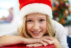 Christmas girl. Portrait of cheerful girl with red giftbox looking at camera on Christmas evening Royalty Free Stock Photos