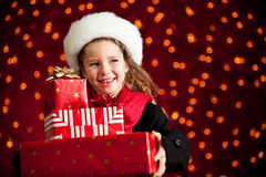 Christmas: Girl With Presents Glances to Side. Beautiful holiday series with a cute girl on a glowing red background, dress in winter clothing.  Suitable for Royalty Free Stock Images