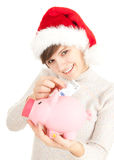Christmas girl putting five euro in piggy bank Royalty Free Stock Photo
