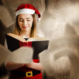 Christmas girl reading open story book. Creative photo of a christmas girl reading open story book with twists and turns from falling pages. Xmas fairy tale Royalty Free Stock Photo