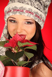 Christmas girl with red flower in her hand Stock Image