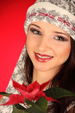 Christmas girl with red flower in her hand Stock Photography