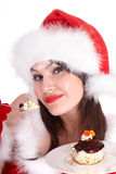 Christmas girl in red santa hat and cake on plate. Stock Image
