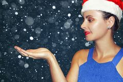 Christmas girl in Santa Claus hat on snowfall background. Beauty fashion model catches snowflakes in palm of hand. Xmas gifts Royalty Free Stock Photos
