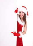 Christmas girl in santa hat with banner point. Royalty Free Stock Image