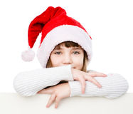 Christmas girl with santa hat behind white board looking at camera. isolated on white Stock Photography