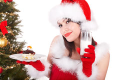 Christmas girl in santa hat and cake on plate. Royalty Free Stock Images