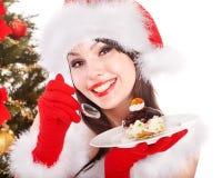 Christmas girl in santa hat eat cake on plate. stock image