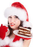 Christmas girl in santa hat eat cake on plate. Royalty Free Stock Photos