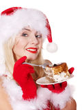 Christmas girl in santa hat eat cake on plate. Royalty Free Stock Image
