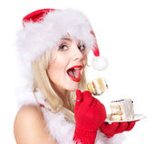 Christmas girl in santa hat eating cake . Royalty Free Stock Photo