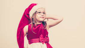 Christmas girl in santa hat festive outfit. Christmas holiday concept. Toddler girl posing, wearing Santa Claus hat and christmassy dress Royalty Free Stock Photos
