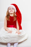 Christmas girl in santa hat festive outfit. Christmas holiday concept. Toddler girl wearing Santa Claus hat and christmassy dress Stock Photography