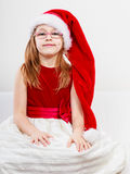 Christmas girl in santa hat festive outfit. Christmas holiday concept. Toddler girl wearing Santa Claus hat and christmassy dress Royalty Free Stock Image