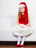 Christmas girl in santa hat festive outfit. Christmas holiday concept. Toddler girl wearing Santa Claus hat and christmassy dress Royalty Free Stock Photos