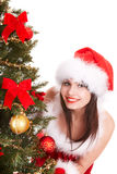 Christmas girl in santa hat with fir tree. Royalty Free Stock Photos