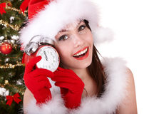 Christmas girl, santa hat, fir tree, alarm clock Royalty Free Stock Photography