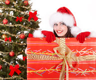 Christmas girl in santa hat, fir tree, gift box. Royalty Free Stock Images