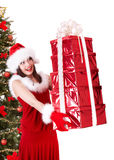 Christmas girl in santa hat, fir tree, gift box. Royalty Free Stock Image