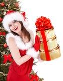 Christmas girl in santa hat, fir tree, gift box. Royalty Free Stock Photography