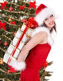 Christmas girl in santa hat,  fir tree, gift box. Stock Image