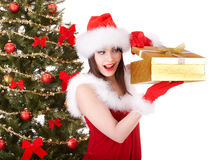 Christmas girl in santa hat, fir tree, gift box. Stock Photo