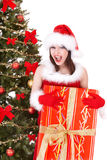 Christmas girl in santa hat with gift box, fir. Royalty Free Stock Photos