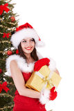 Christmas girl in santa hat with gift box. Tree. Stock Photography