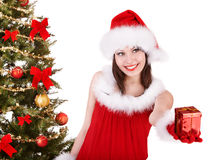 Christmas girl in santa hat giving  gift box. Royalty Free Stock Images