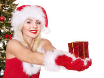 Christmas girl in santa hat giving red gift box. Royalty Free Stock Image