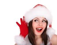 Christmas girl in santa hat, hand near ear listen. Stock Photo