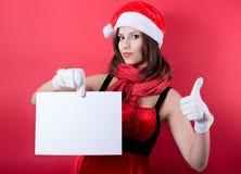 Christmas girl in santa hat holding banner. Stock Photo