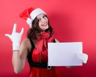 Christmas girl in santa hat holding banner. Royalty Free Stock Image