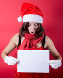 Christmas girl in santa hat holding banner. Royalty Free Stock Images