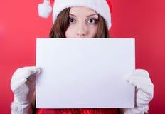 Christmas girl in santa hat holding banner. Stock Images