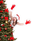 Christmas girl in santa hat near tree hand up. Stock Images