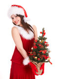Christmas girl in santa hat with small tree. Royalty Free Stock Photo