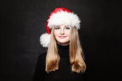 Christmas Girl in Santa Hat Smiling Stock Images