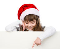 Christmas girl with santa hat standing behind white board.  Stock Images
