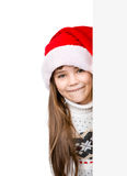 Christmas girl in santa helper hat peeping from behind empty board.  isolated on white background Stock Images