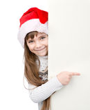 Christmas girl in santa helper hat pointing on blank white board. isolated Stock Photos