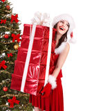 Christmas girl in santa holding stack gift box. Royalty Free Stock Image